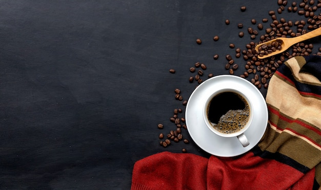 Xícara de café no fundo do assoalho de madeira preta. conceito de inverno, vista de cima