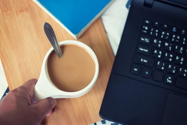 Xícara de café no laptop de madeira