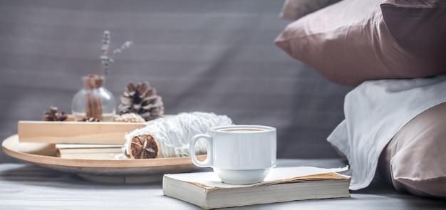 Xícara de café no livro e elementos decorativos em uma bandeja de madeira