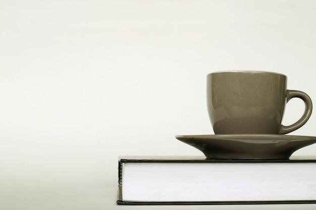 Xícara de café no livro sobre fundo branco