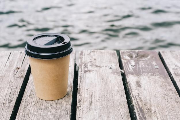 Xícara de café no mar e madeira marrom