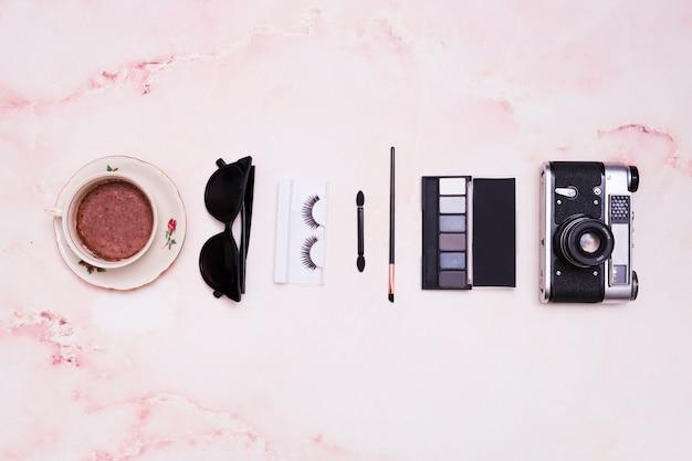 Xícara de café; oculos escuros; cílios; pincel de maquiagem; paleta da sombra e câmera vintage no pano de fundo texturizado rosa