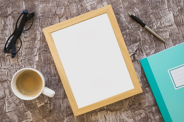 Xícara de café; óculos; porta-retrato; caneta e caderno no plano de fundo texturizado