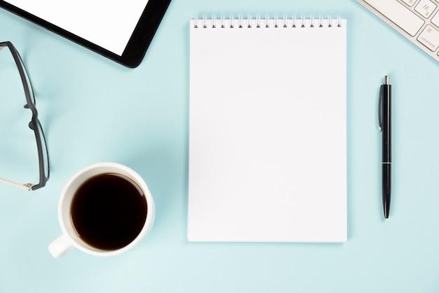 Xícara de café; óculos; tablet digital; teclado; bloco de notas e caneta espiral em branco sobre fundo azul