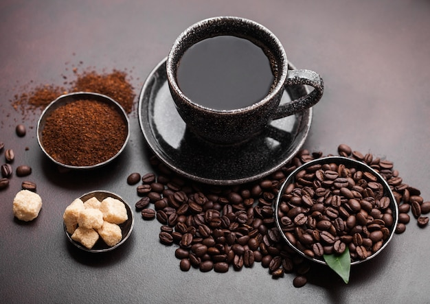 Xícara de café orgânico cru fresco com feijão e pó moído com cubos de açúcar de cana com folha de cafeeiro em fundo escuro.