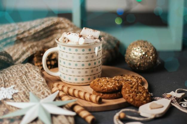 Xícara de café ou cacau com marshmallows, paus de canela, manta de malha e brinquedos de natal.
