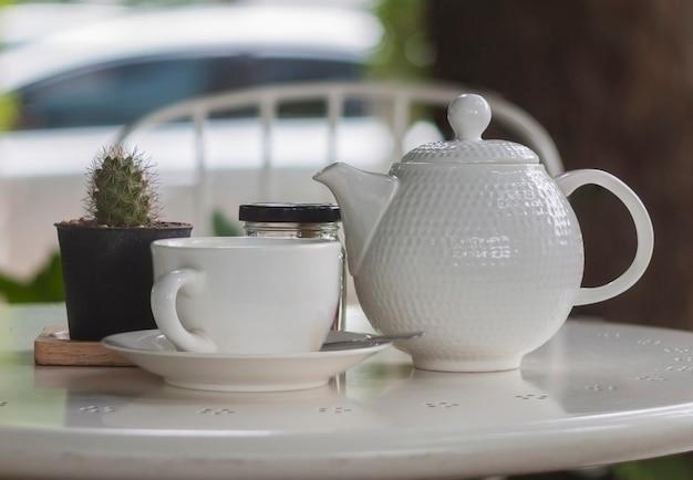 Xícara de café ou chá branca na mesa branca com pequeno cacto