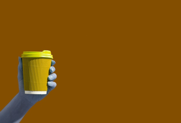 Xícara de café ou chá de papelão na mão da mulher em um fundo de mostarda com espaço de cópia. bebidas quentes para levar conceito minimalista