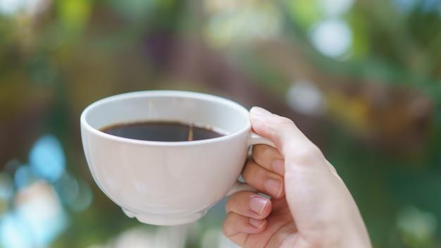 Xícara de café ou chá na mão da mulher