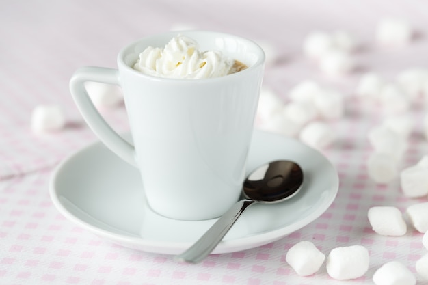 Xícara de café ou chocolate quente com chantilly em cima da mesa no café