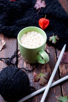 Xícara de café ou chocolate quente com marshmallow perto de cobertor de malha e agulhas de tricô