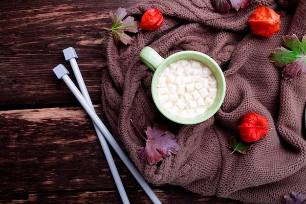Xícara de café ou chocolate quente com marshmallow perto do cobertor de malha e agulhas.