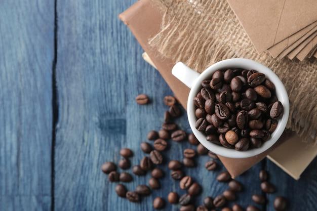 Xícara de café para café expresso e grãos de café em uma mesa de madeira azul com lugar para texto. vista do topo