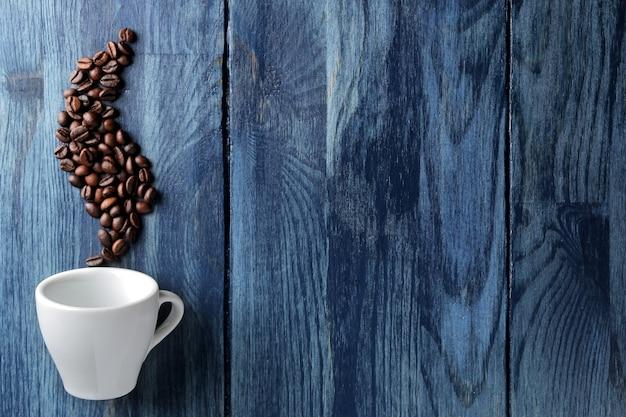 Xícara de café para expresso e grãos de café em forma de fumaça em uma mesa de madeira azul com espaço para uma inscrição