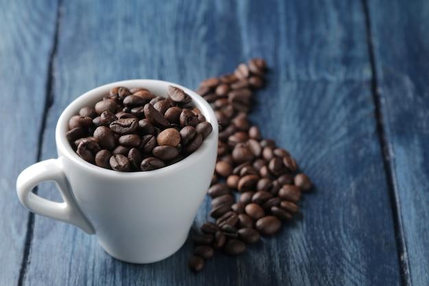Xícara de café para expresso e grãos de café em uma mesa de madeira azul com espaço para inscrição