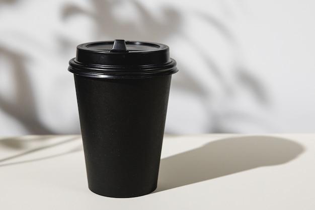 Xícara de café para viagem com sombras de folhagem, copie o espaço
