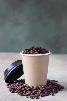 Xícara de café para viagem e grãos de café torrados. conceito de cafeteria.