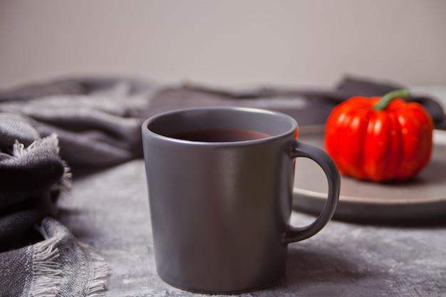 Xícara de café, pequena abóbora no concreto