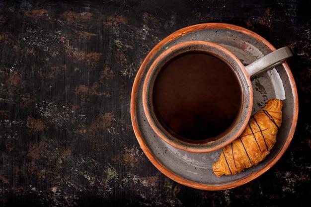 Xícara de café perfumado e um croissant. cafe da manha. lay plana. vista do topo