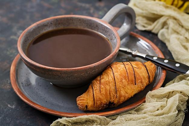 Xícara de café perfumado e um croissant. cafe da manha