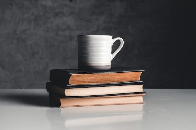 Xícara de café perto da pilha de livros em fundo cinza