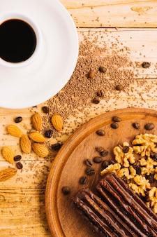 Xícara de café perto de nozes na tábua de cortar