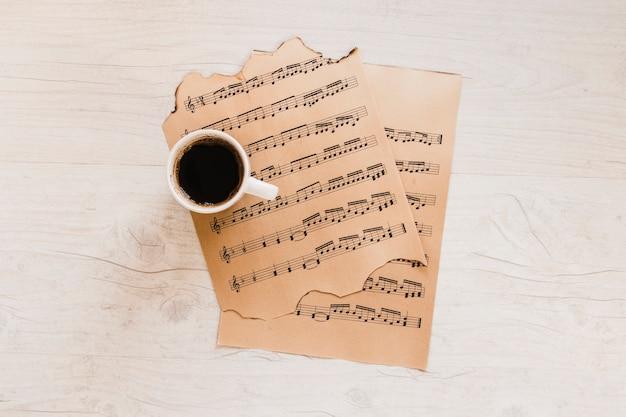 Xícara de café perto de partituras