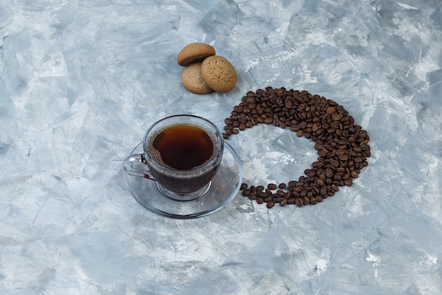Xícara de café plana leigos, biscoitos com grãos de café sobre fundo de mármore azul claro. horizontal