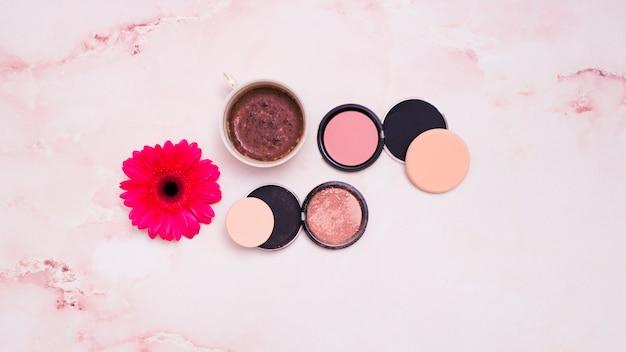 Xícara de café; pó facial compacto com puff; flor gerbera vermelha no pano de fundo texturizado rosa