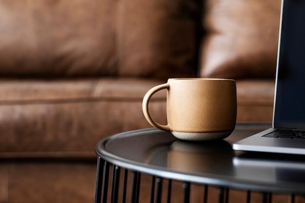 Xícara de café por um laptop