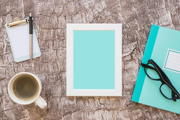 Xícara de café; porta-retrato; caderno; óculos e prancheta em miniatura com caneta