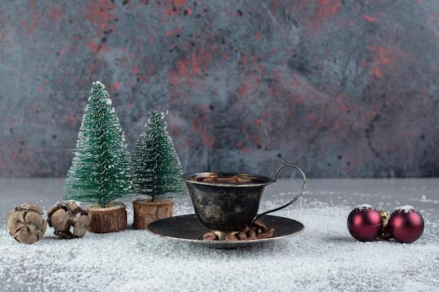 Xícara de café preta com decorações de natal em pó de coco na superfície de mármore