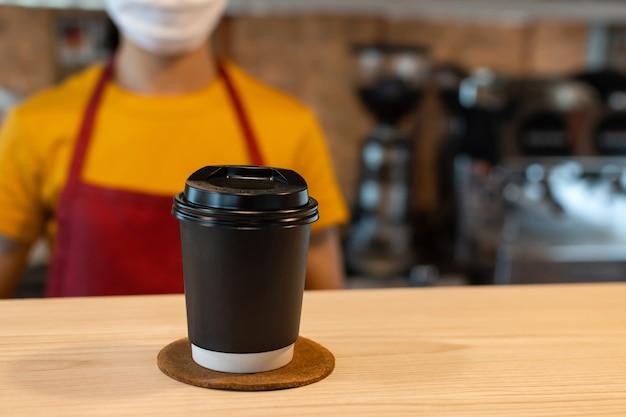 Xícara de café preta quente no balcão com equipe de garçonete usando máscara facial de proteção no fundo em uma cafeteria, entrega de comida, restaurante de café, comida para viagem, proprietário de uma pequena empresa, conceito de comida e bebida