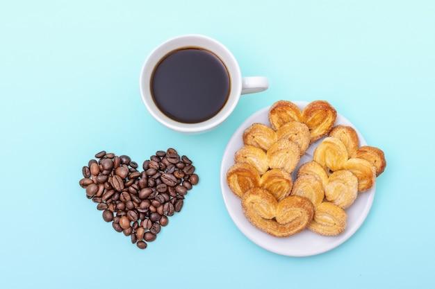 Xícara de café preto, biscoitos em forma de coração, grãos de café em forma de coração em um fundo azul