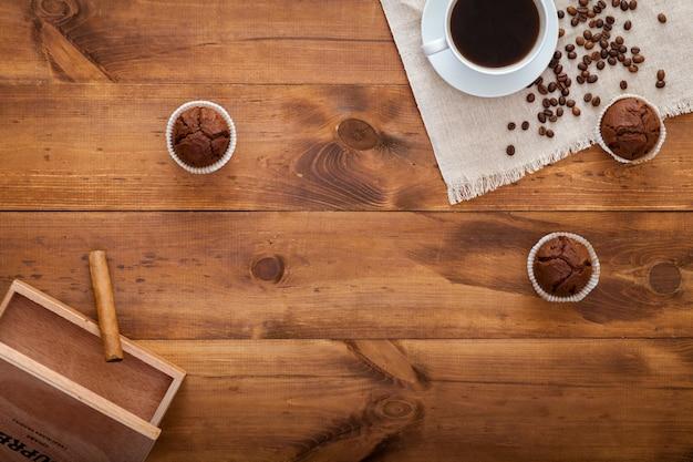 Xícara de café preto, bolos e grãos de café espalhados na mesa de madeira marrom