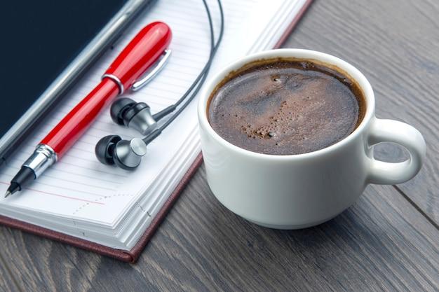 Xícara de café preto, caneta, telefone celular, caderno e fones de ouvido estão na mesa