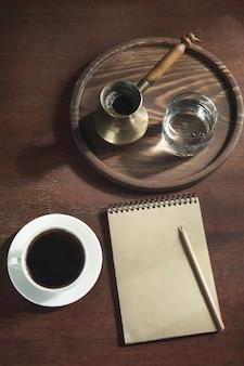 Xícara de café preto, cezve de cobre e água em um copo na bandeja de madeira em estilo vintage.