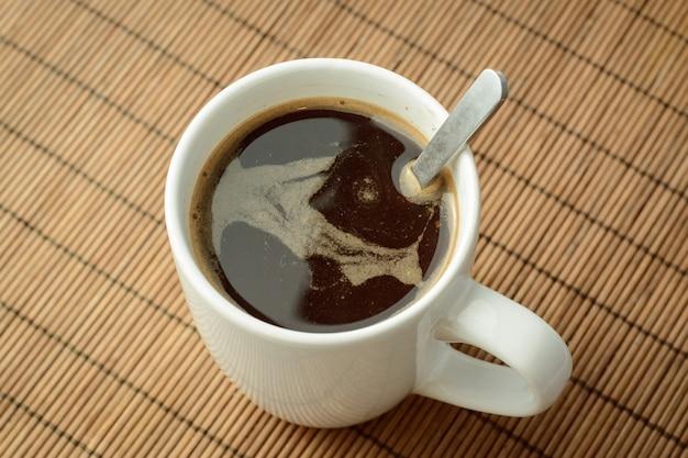 Xícara de café preto com colher em brown