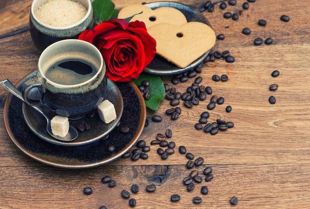 Xícara de café preto com flor rosa vermelha e bolo de coração em fundo de madeira. imagem em tons de estilo retro