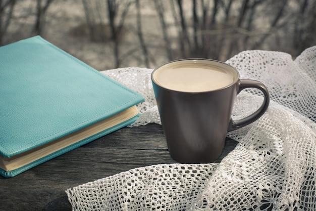 Xícara de café preto com leite em frente à janela de manhã