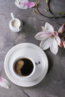 Xícara de café preto com magnólia