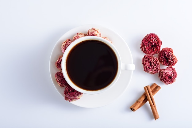 Xícara de café preto com rosas no prato, paus de canela na mesa branca