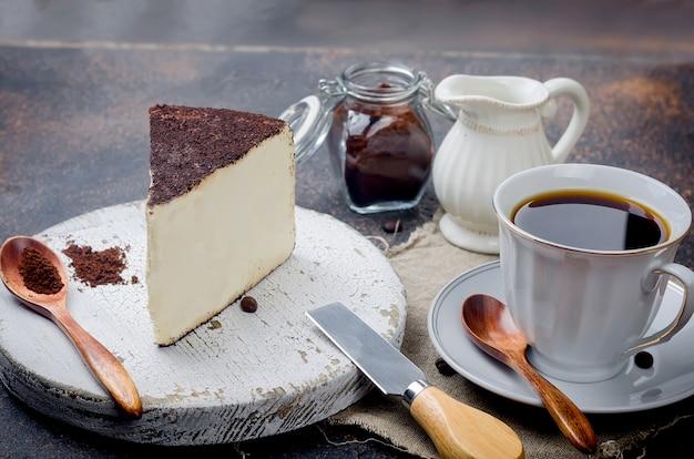 Xícara de café preto com um pedaço de queijo no café moído