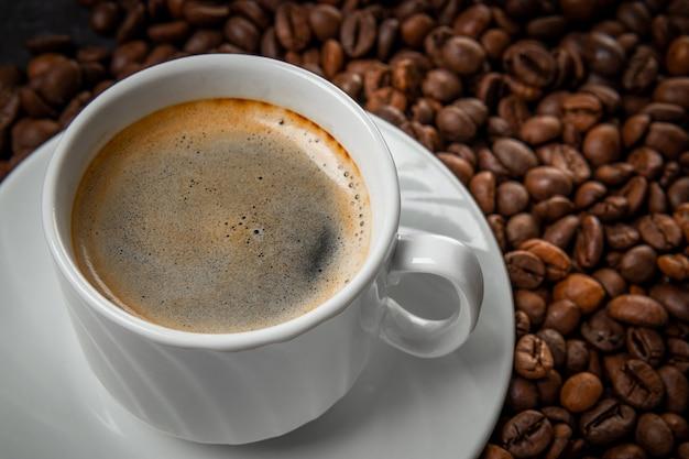 Xícara de café preto e grãos de café torrados close-up.