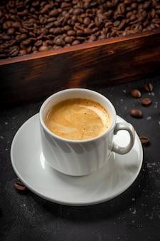 Xícara de café preto e grãos de café torrados em uma foto vertical de caixa de madeira.