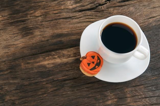 Xícara de café preto e uma abóbora de biscoito de halloween fica em uma mesa de madeira marrom. conceito de comida de halloween. copie o espaço