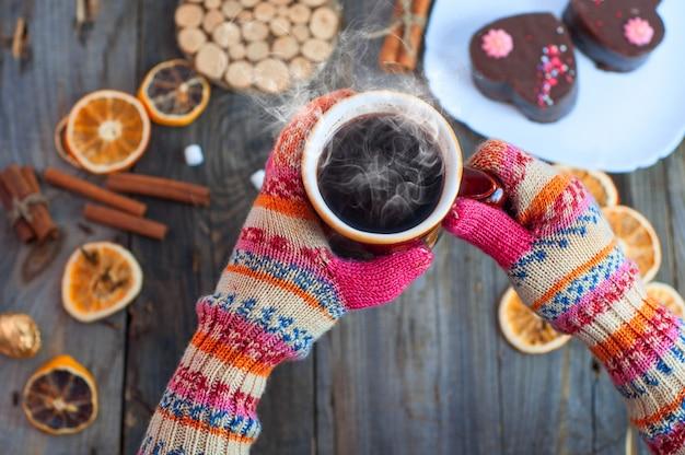 Xícara de café preto em suas mãos sobre a mesa