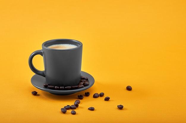 Xícara de café preto em um fundo amarelo conceito bom dia, impulso de energia, motivação