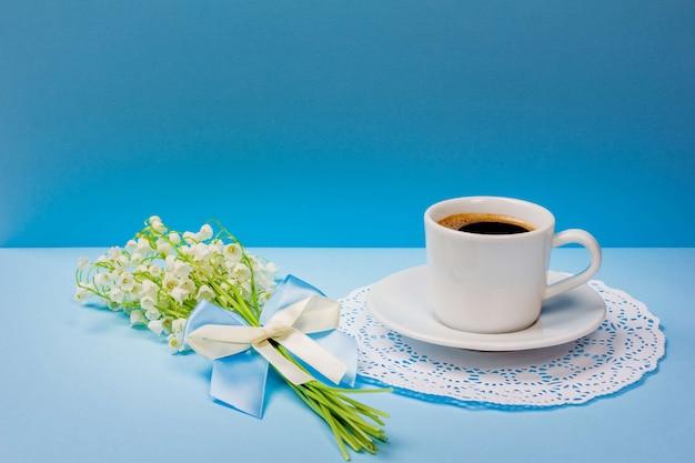 Xícara de café preto em um pires e um buquê de flores de lírio do vale