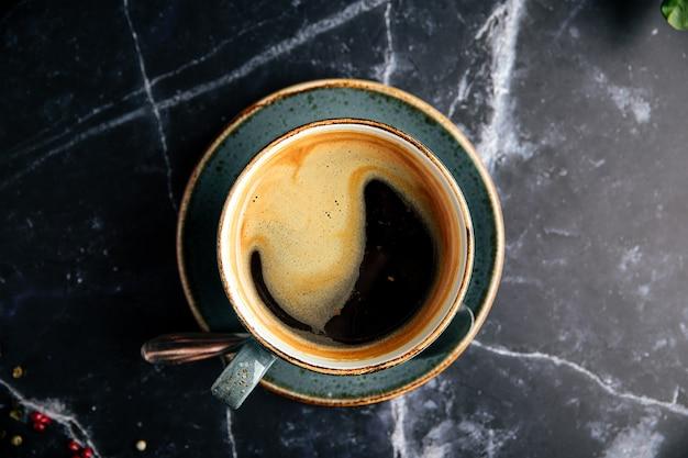 Xícara de café preto fresco na mesa de mármore escuro